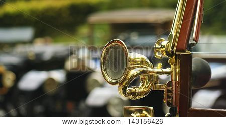An Antique Brass Car Horn on the Windshield of a Vintage Automobile