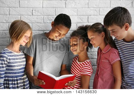 Cute kids reading book with flashlight