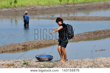 Ayutthaya Thailand - December 19 2010: Thai woman wearing a backpack fishing in flooded pools divided by earthen berms
