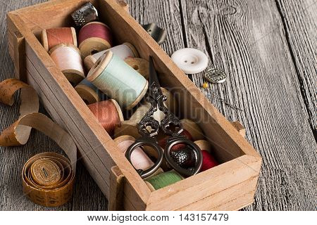 Wooden box with sewing utensils, a measuring tape, buttons and needles on gray wooden table.