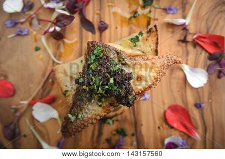 Canape - fish and olive tapenade on board with petals