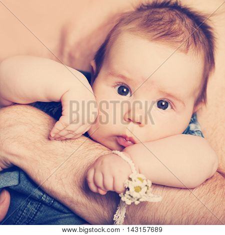 Little beautiful baby girl on father's hands