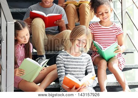 Cute kids reading books on stairs