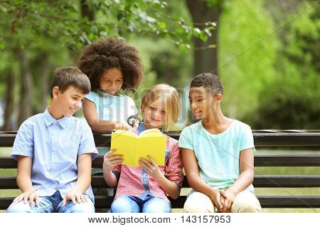Cute kids reading book on bench