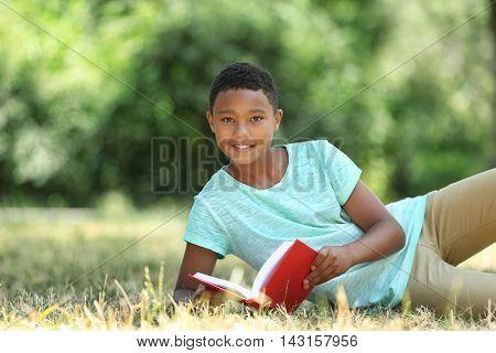 Cute boy reading book on green grass