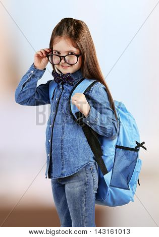 Cute girl wearing glasses and backpack on blurred background. Education concept.