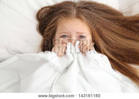 Cute little girl hiding under white bed sheet