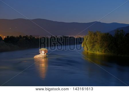 wooden house on a rock of Drina River by night, Serbia