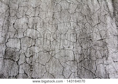Eroded old grey plaster at a wall for dirty scratched texture background