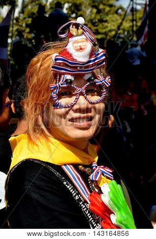 Bangkok Thailand - January 13 2014: Woman wearing red white and blue oversize glasses at the Shut Down Bangkok anti-government protest