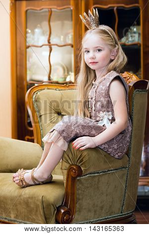 Little girl with crown on the chair