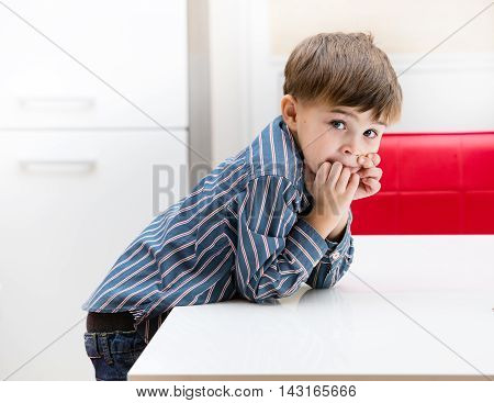 The boy in the kitchen at the table