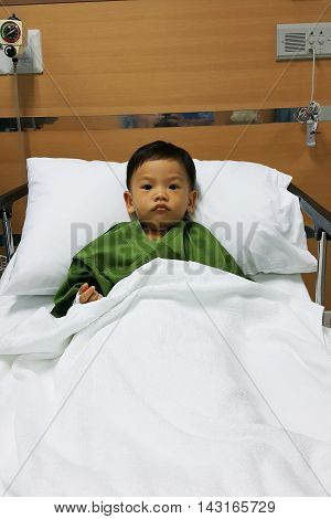Asian sick boy on hospital bed with saline intravenous (IV) on hand