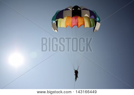 A background with an abstract view of a colorful parasailing parachute near the bright sun.