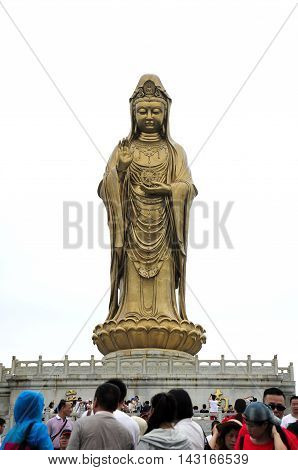July 19 2015. Putuoshan China. Chinese tourists below the large bronze Guanyin sea goddess Buddha statue on the island of Putuoshan located in Zhejiang Province China.