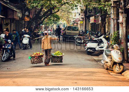 Hanoi, Vietnam - 21 December,2014: The street vendor walk across the street