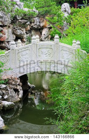 A curved bridge over a small stream within the classical Chinese li yuan garden in Zhaojialou in Shanghai china on an overcast day.