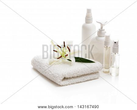 Flower white Lily lying on a towel and bottles