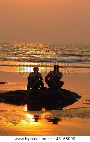 Two friends watching the sea in the evening sadly as they bid farewell to their summer vacation