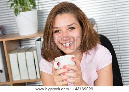 Woman At Office Desk With Laptop And Cup Of Coffee