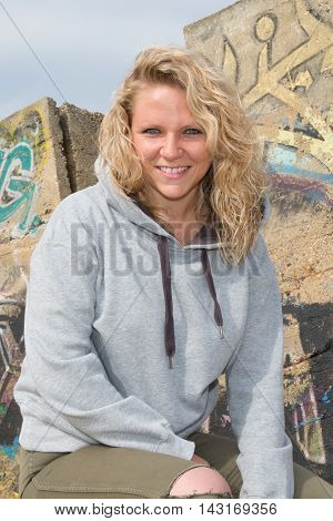 Beautiful Young Fashion Model In Grey Against The Wall With Graffiti
