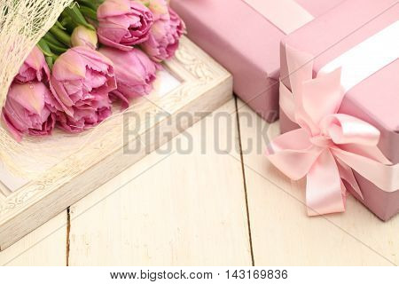 Flowers and gift box on wooden background with copyspace