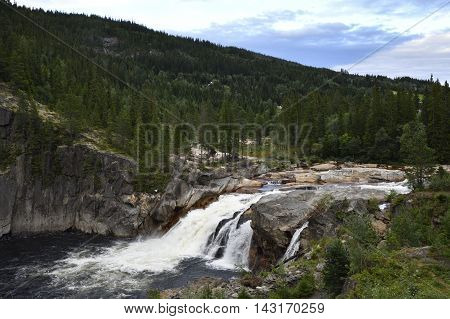 Waterfall with white water and surrounding forest from the North of Norway.