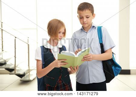 Cute schoolkids on light background