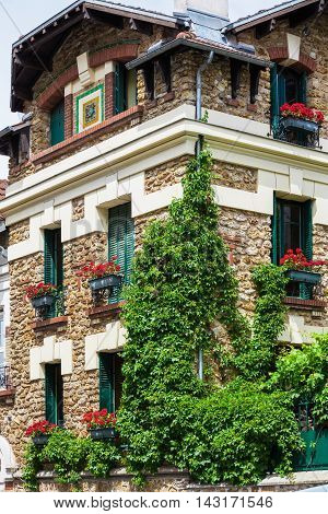 Wonderful picturesque house covered by ivy with geraniums fill boxes on the Montmartre hill Paris France