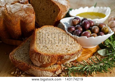 Freshly baked homemade sourdough spelt bread extra virgin olive oil and olives on olive wood plank