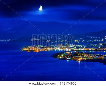 Agios Nikolaos at night Crete Greece. Agios Nikolaos is a picturesque town in the eastern part of the island Crete built on the northwest side of the peaceful bay of Mirabello.