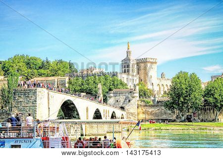 AVIGNON, FRANCE - MAY 08 2014: tourists in the Avignon's boat taking pictures of Avignon's bridge and The Popes Palace in Avignon ( city of Popes) France