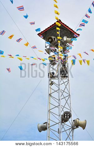 The public loudspeaker and cctv on tower decorate with Thailand flag and Buddhism flag.