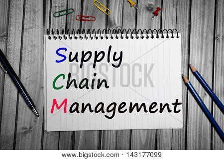 The words Supply Chain Management on white ring binder notebook