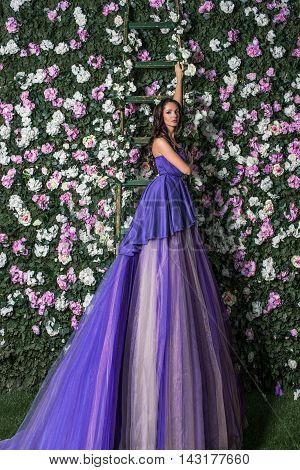 Beautiful brunette woman wearing long purple dress posing in the flowered garden