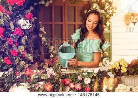 Beautiful young brunette woman in mint dress watering flowers on a porch of her house