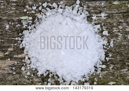 White salt on rustic wooden table closeup