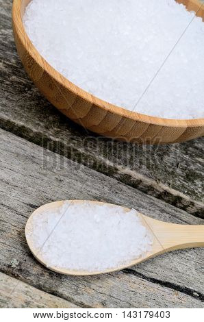 White salt in wooden spoon on table
