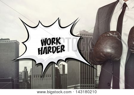 Work harder text on speech bubble with businessman wearing boxing gloves