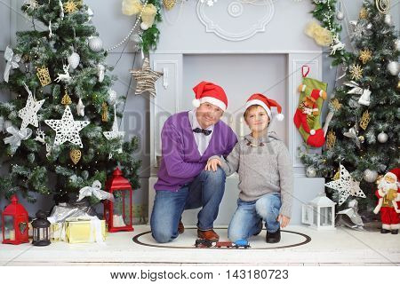 Father with his son in santa caps sit with toy railway near christmas tree