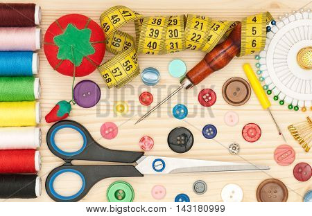 Bright sewing accessories over wooden surface close-up