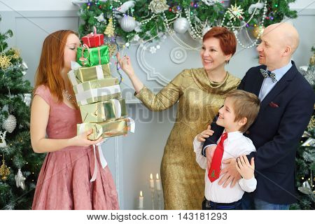 Husband, wife, son look and daughter woth many gifts during christmas, focus on girl