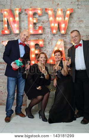 Four happy friends drink wine near illuminated letters (New Year)