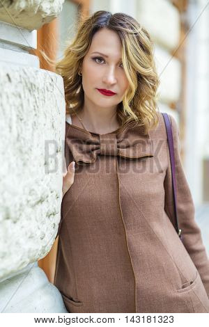 Pretty middleaged woman in jacket poses near building wall outdoor, shallow dof