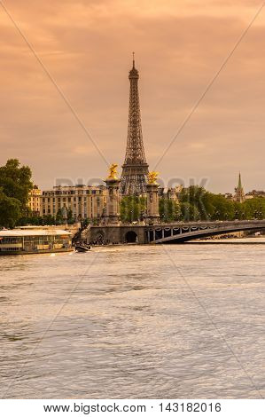 PARIS FRANCE - MAY 07 2015: Tour Eiffel and Pont Alexandre III bridge over the river Seine in the dusk Paris France