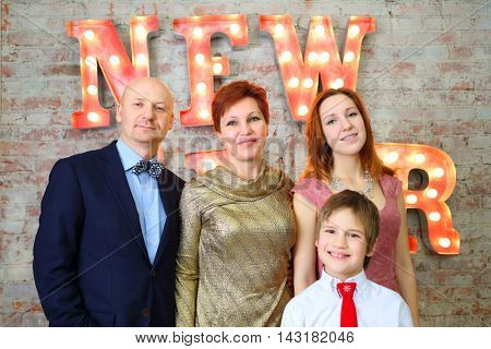 Father, mother, daughter and son pose near big letters New Year in studio