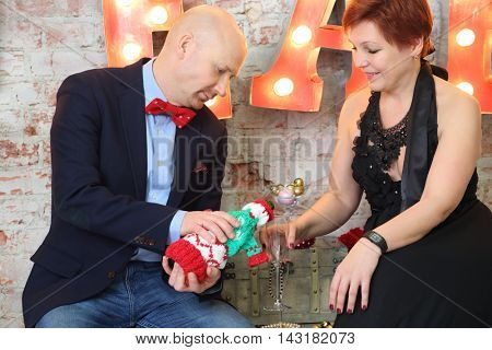 Bald man pours white wine for woman near wall with big letters
