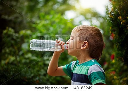 Little boy drinking mineral water from the plastic bottle on outdoor.
