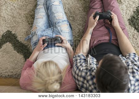 Top view of a couple in love enjoying their free time sitting on the floor next to a couch playing video games and having fun. Focus on guy's hands