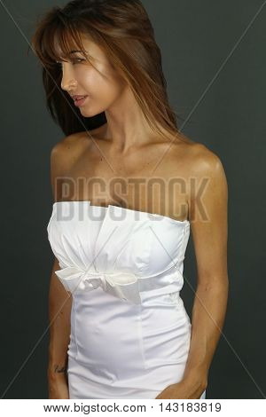 Beautiful woman wearing a white dress over a gray background